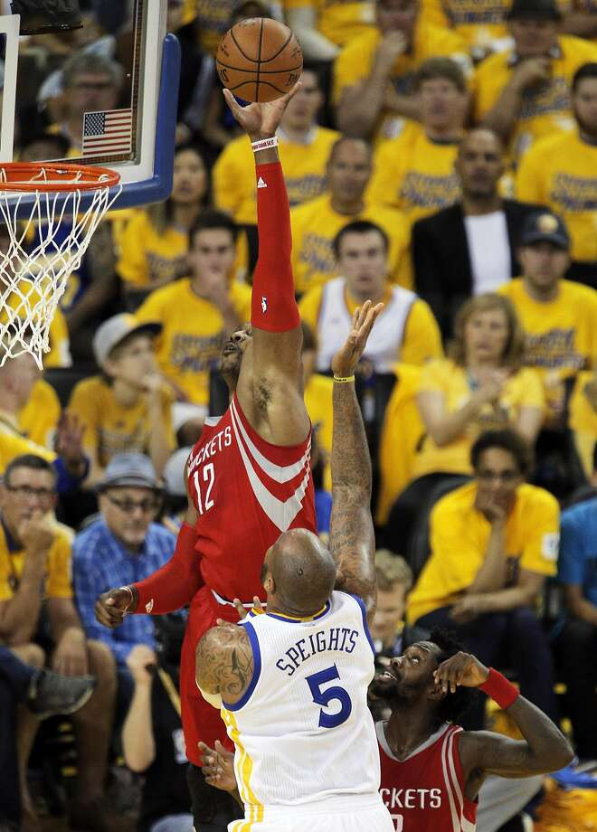 Dwight Howard (12) bats away a shot by Marreese Speights (5) but the basket was called good in the first half as the Golden State Warriors played the Houston Rockets in game 2 of the first round of the Western Conference Playoffs at Oracle Arena in Oakland, Calif., on Monday, April 18, 2016. Photo: Carlos Avila Gonzalez, The Chronicle