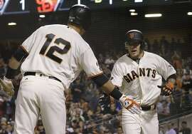 San Francisco Giants' Jake Peavy, right, is congratulated by Joe Panik (12) after scoring against the Arizona Diamondbacks during the second inning of a baseball game in San Francisco, Monday, April 18, 2016. (AP Photo/Jeff Chiu)