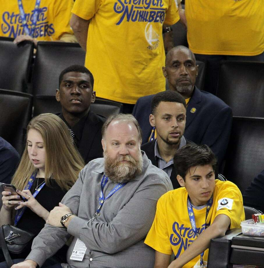 Stephen Curry (30) watches from behind fans in the second half as the Golden State Warriors played the Houston Rockets in game 2 of the first round of the Western Conference Playoffs at Oracle Arena in Oakland, Calif., on Monday, April 18, 2016. Photo: Carlos Avila Gonzalez, The Chronicle