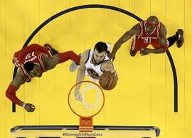 Andrew Bogut (12) taps in a rebound for a basket while guarded by Dwight Howard (12) and Jason Terry (31) in the second half as the Golden State Warriors played the Houston Rockets in game 2 of the first round of the Western Conference Playoffs at Oracle Arena in Oakland, Calif., on Monday, April 18, 2016.