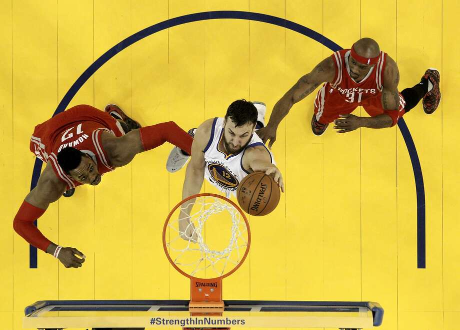 Andrew Bogut taps home a rebound between Houston's Dwight Howard (12) and Jason Terry. The Warriors' center went 5-for-6 from the floor in Golden State's 115-106 victory Monday. Photo: Carlos Avila Gonzalez, The Chronicle