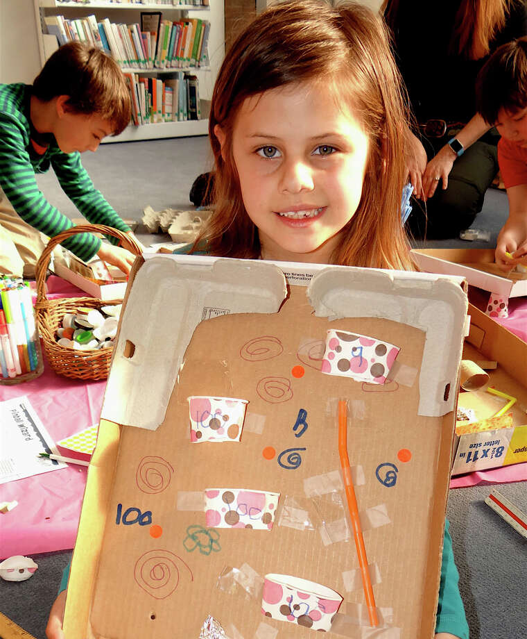 "Gabriella Juliano, 6, shows off the pinball ""machine"" that she made last week at a Pequot Library workshop. Photo: Fairfield Citizen / Mike Lauterborn / Fairfield Citizen"