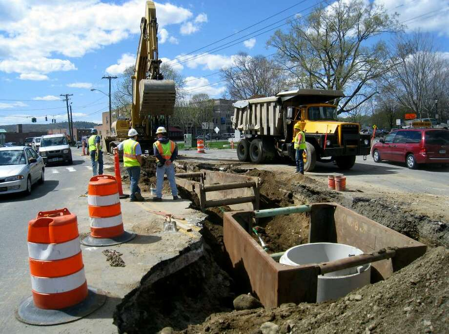 SPECTRUM/Drainage work on Bridge Street in New Milford from the Village Green to the new Grove Street/Route 67 intersection was expected to be completed Wednesday or yesterday (Thursday). Above, motorists warily pass on both sides Monday while new drainage pipes are placed under the middle of the street as part of the Grove Street/Route 67 realignment project. April 12, 2010 Photo: Norm Cummings / The News-Times