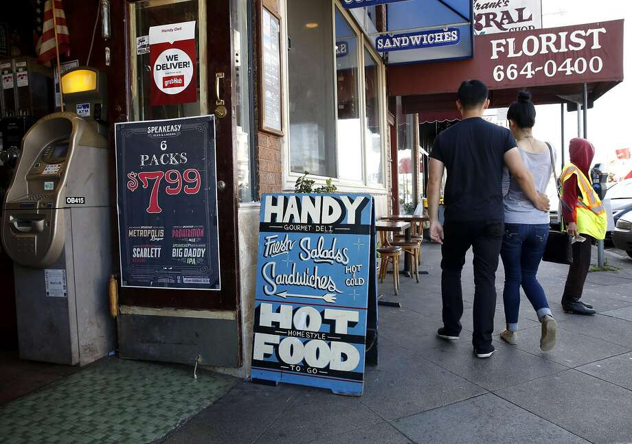 A couple walk past Handy Deli on Irving Street in the Sunset neighborhood of San Francisco. Photo: Connor Radnovich, The Chronicle