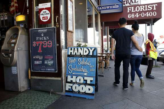 A couple walks past Handy Deli on Irving Street in the Sunset neighborhood of San Francisco, California, on Sunday, April 17, 2016.
