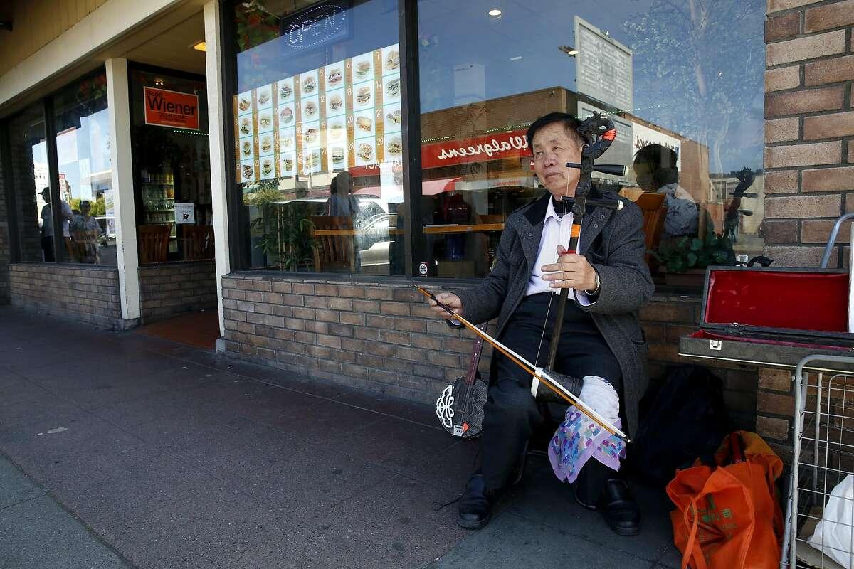 A man plays an Erhu on Irving Street in the Sunset neighborhood of San Francisco, California, on Sunday, April 17, 2016.