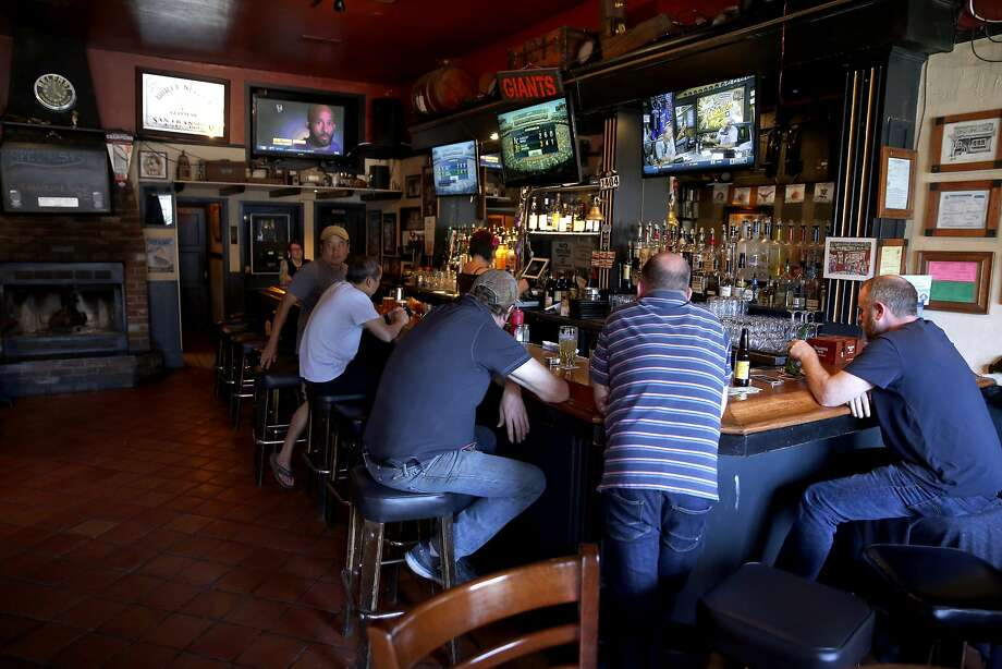 Men crowd around the bar inside Durty Nelly's in the Sunset neighborhood of San Francisco. Photo: Connor Radnovich, The Chronicle