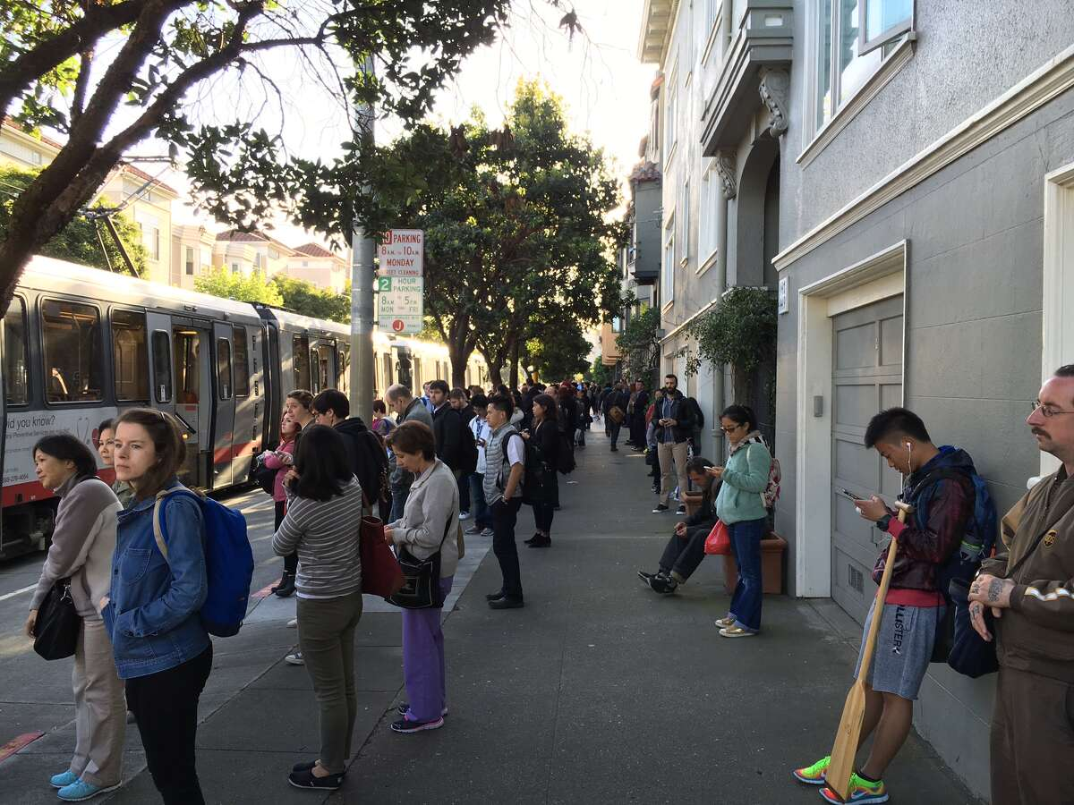 Stranded commuters wait in along Carl Street in San Francisco's Cole Valley after Muni's N-Judah inbound trains were delayed Tuesday morning.