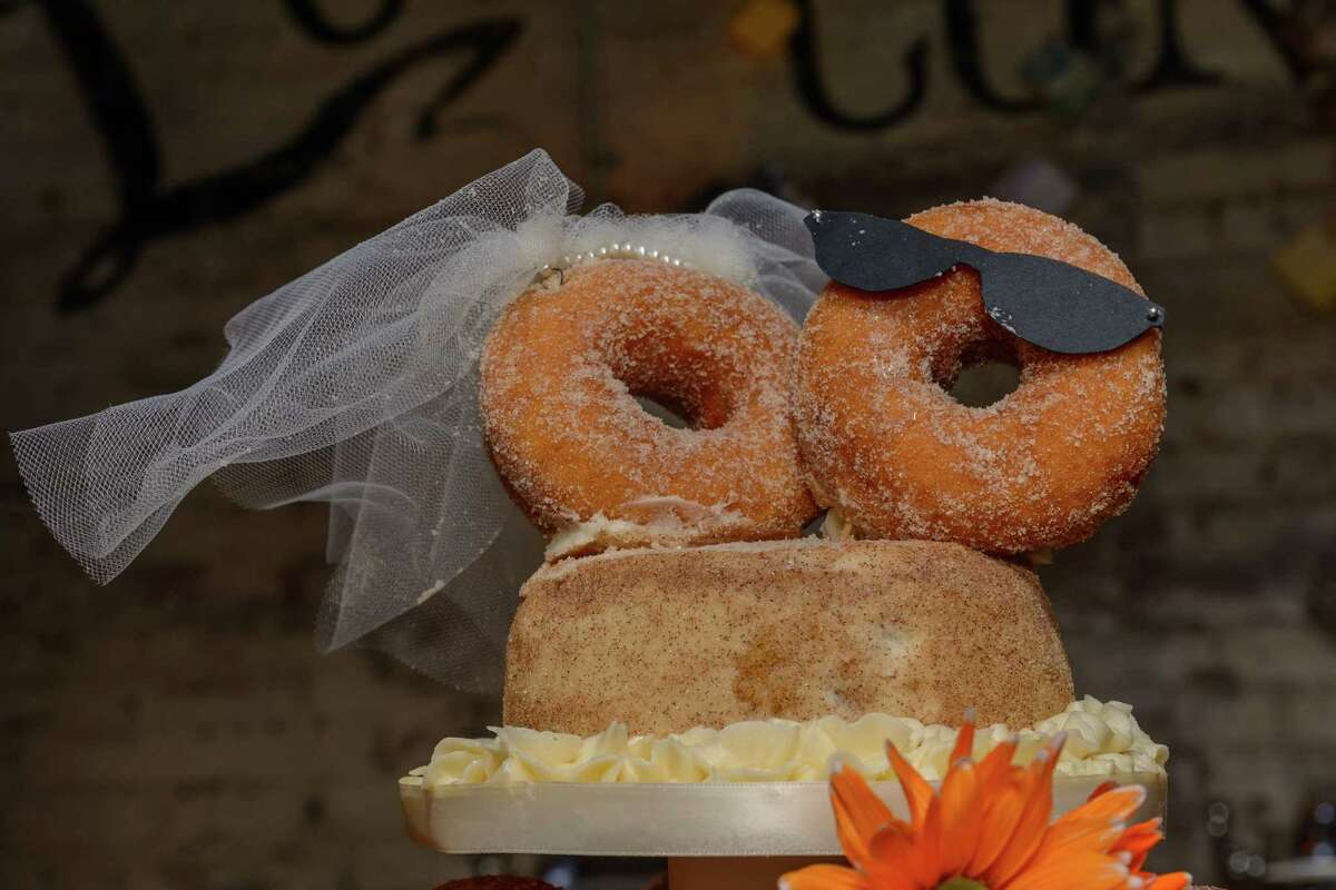 A bride and groom cider donut topper at top of Brianna Snyder and David Deyette's creative Apple Cider Donut cake, made by a co-worker, at their reception on September 27, 2014. (Trinacria Photography)