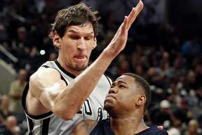 San Antonio Spurs' Boban Marjanovic defends Memphis Grizzlies' Jarell Martin during second half action of Game 1 in the first round of the Western Conference playoffs Sunday April 17, 2016 at the AT&T Center. The Spurs won 106-74.