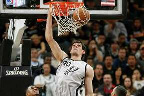 SAN ANTONIO, TX - APRIL 17: Boban Marjanovic #40 of the San Antonio Spurs dunks in front of Jordan Farmar #4 of the Memphis Grizzlies during Game One of the Western Conference Quarterfinals during the 2016 NBA Playoffs at AT&T Center on April 17, 2016 in San Antonio, Texas.  NOTE TO USER: User expressly acknowledges and agrees that by downloading and or using this photograph, User is consenting to the terms and conditions of the Getty Images License Agreement.