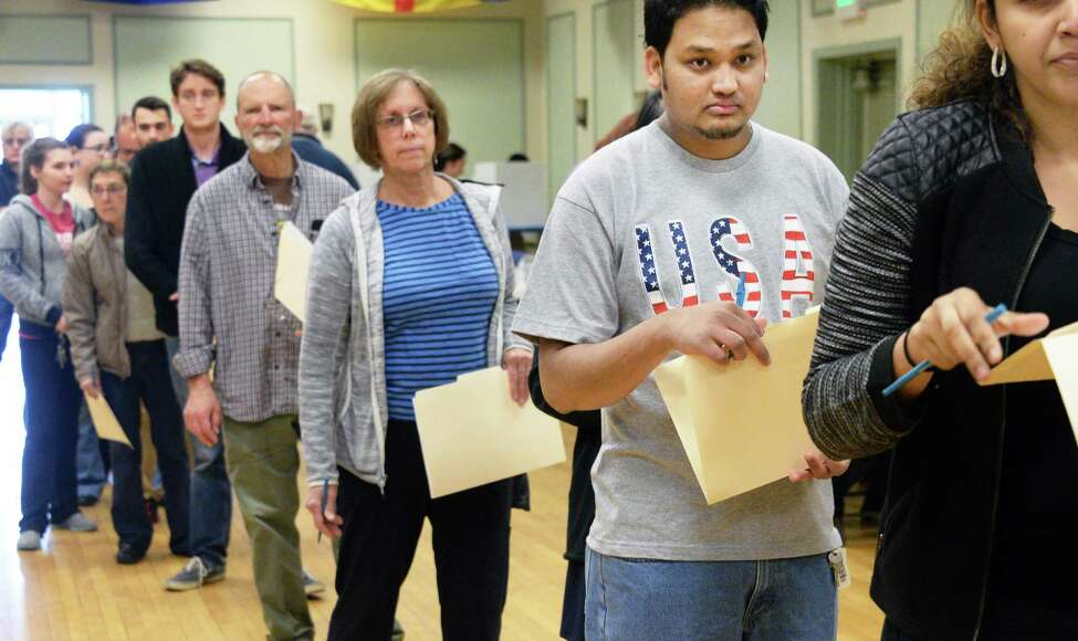 Santosh Baraily,right, a refugee form Bhutan, waits in line to cast his first ever vote at the Ancient Order of Hibernians Tuesday April 19, 2016 in Albany,NY. (John Carl D'Annibale / Times Union)