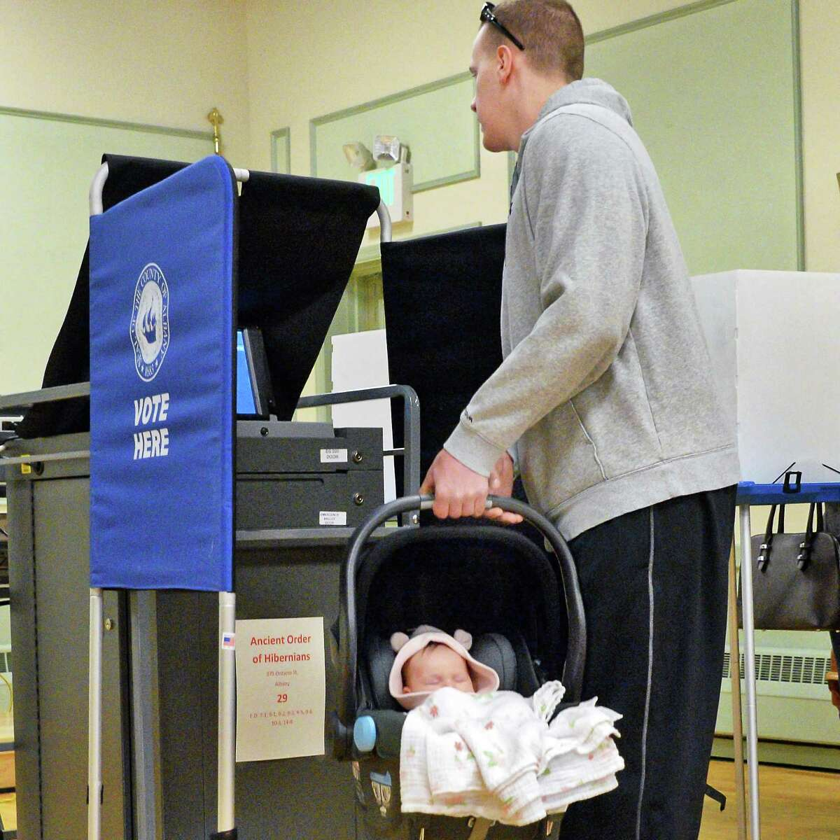 Ryan Lawson cries his 2-month-old daughter Beatrice Lawson as he casts his vote in the New York presidential primary at the Ancient Order of Hibernians Tuesday April 19, 2016 in Albany,NY. (John Carl D'Annibale / Times Union)