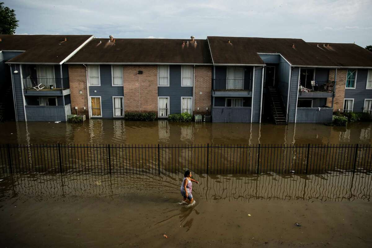 A woman walks through flood waters in front of the Arbor Court Apartments on Monday, April 18.