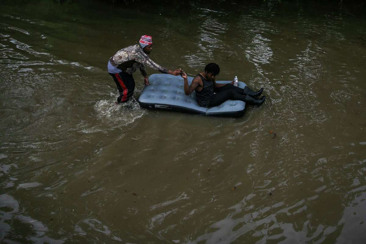 A man riding on an inflatable mattress passes a cigarette to the man pushing as they navigate the flooded Greenspoint area Monday, April 18, 2016 in Houston.