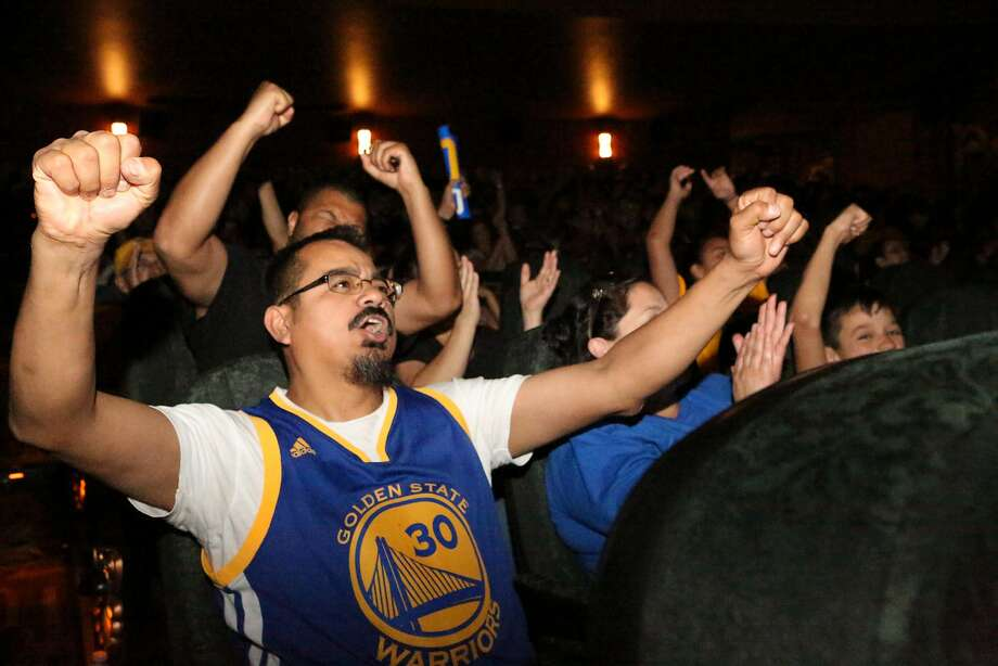 Above: Warriors fan Moises Tapia of Alameda cheers at the Alameda Theatre while watching Mon day's game. Movie the aters have become an ideal venue for fans to watch  costly sporting events. Photo: Amy Osborne, Special To The Chronicle