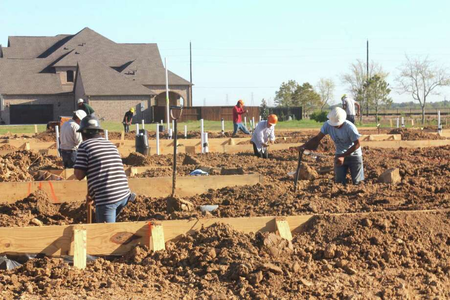 Workers build a foundation for a luxury Toll Brothers home in the Legend section of Cane Island at 2100 Cane Island Parkway in Katy. Photo: Suzanne Rehak, Freelance Photographer