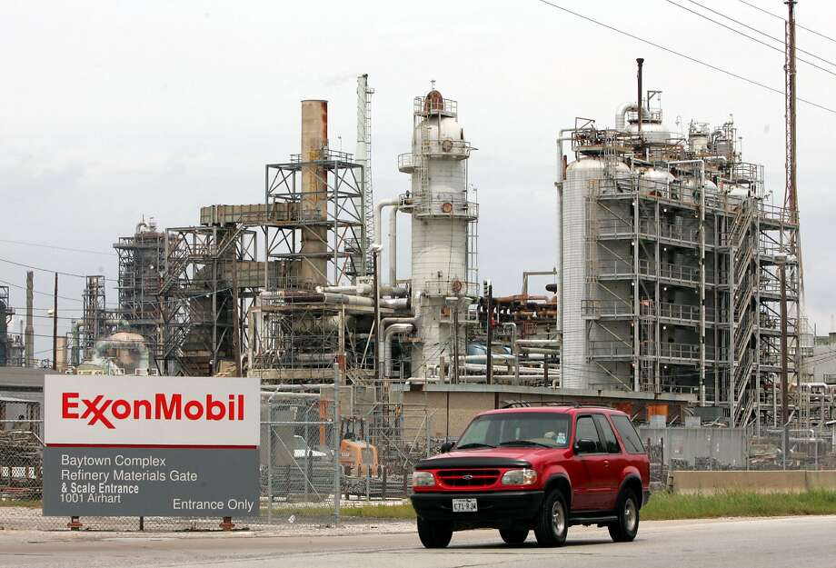 In this April 4, 2005 file photo, a sports utility vehicle drives past an ExxonMobil refinery in Baytown, Texas. Exxon Mobil Corp., the world's biggest oil refiner, will spend more than $1 billion in the next couple of years to increase its global production of cleaner-burning diesel by about 10 percent, the company said Tuesday, Dec. 16, 2008. Exxon Mobil, which had $37 billion in cash at the end of the third quarter, will expand production at its refineries in Baton Rouge, La., Baytown, Texas, and Antwerp, Belgium. Baytown is the largest U.S. refinery. (AP Photo/File) Photo: AP