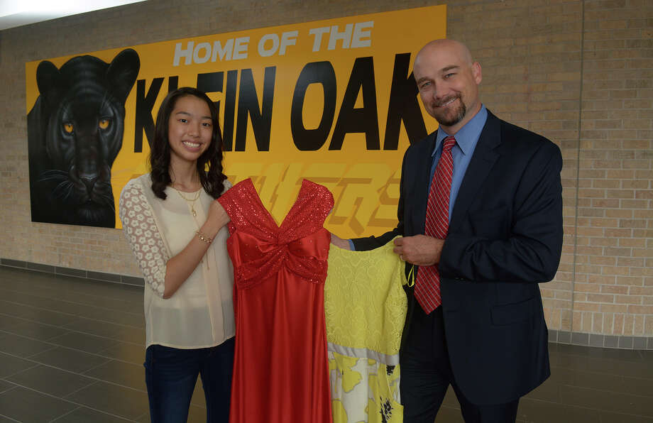 Klein Oak High School sophomore Emily Nguyen and principal Brian Greeney hold some of the prom dresses that Nguyen donated to Giving Gown. Photo: Jerry Baker, Freelance