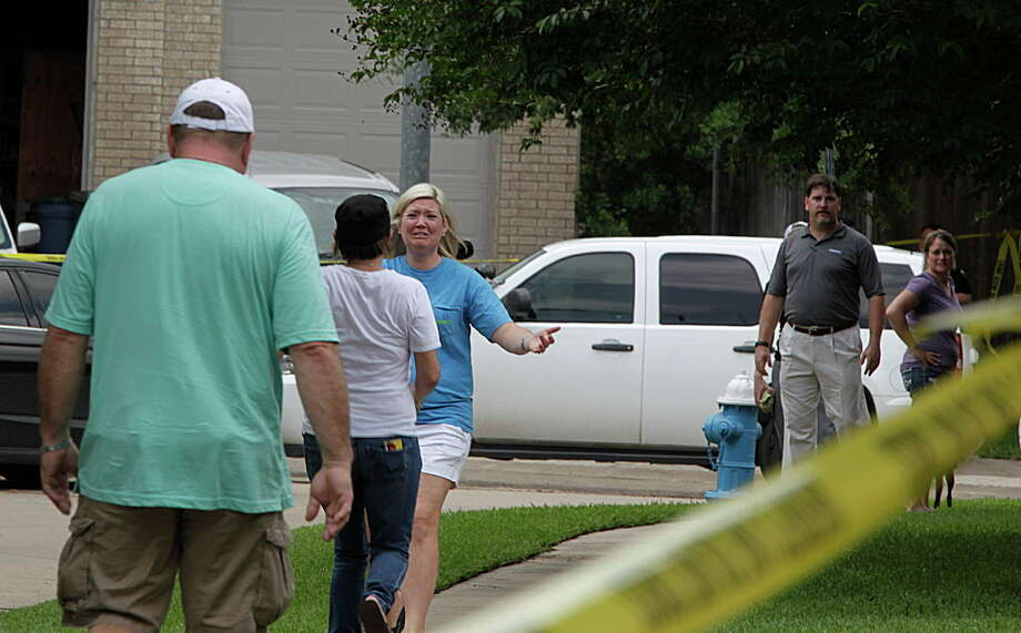 An unidentified woman reaches out to embrace Tracee  Dugal, center. Her husband, Thomas Dugal, follows as Fort Bend County Sheriff's Office deputies investigate a murder-suicide involving two adults and two children who were friends of the Dugals, at a home in the 1300 block of Longdraw in Katy, Tuesday, April 19, 2016. Photo: James Nielsen, Houston Chronicle / © 2016  Houston Chronicle