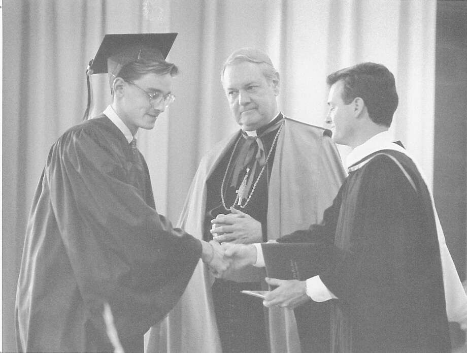 Michael Bothwell, is congratulated on receiving his diploma from St. Mary's High School by James C. Stanley, headmaster, and the Most Rev. Edward M. Egan, bishop of Bridgeport on June 1, 1990. Photo: Steve Daniel