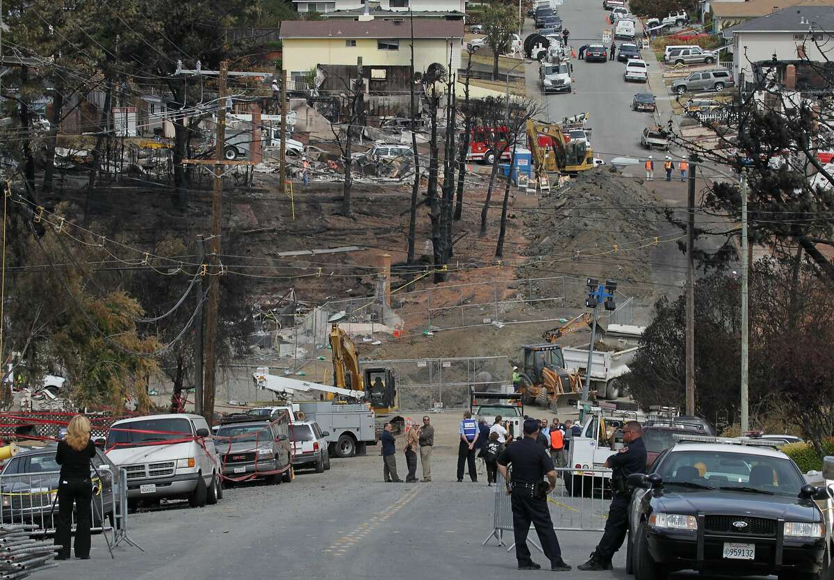 FILE-- Officials look on as Pacific Gas & Electric workers excavate the crater at the epicenter of a deadly gas main explosion September 13, 2010 in San Bruno, California. State regulators have ordered Pacific Gas & Electric to inspect all of their gas lines following a deadly blast that destroyed thirty eight homes, severely damaged dozens more and killed at least four people in a San Bruno, California neighborhood near San Francisco International Airport on Thursday evening.