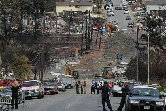 SAN BRUNO, CA - SEPTEMBER 13:  Officials look on as Pacific Gas & Electric workers excavate the crater at the epicenter of a deadly gas main explosion September 13, 2010 in San Bruno, California. State regulators have ordered Pacific Gas & Electric to inspect all of their gas lines following a deadly blast that destroyed thirty eight homes, severely damaged dozens more and killed at least four people in a San Bruno, California neighborhood near San Francisco International Airport on Thursday evening.  (Photo by Justin Sullivan/Getty Images)