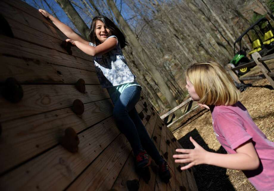 Lola Dellascenza, left, of Cos Cob School, and Maggie Saleeby, of North Street School, climb the bouldering wall during Greenwich Public Schools' Orienteering Adventure Days at the Camp Seton Scout Reservation in Greenwich, Conn. Tuesday, April 19, 2016. Led by P.E. teachers and staff from Camp Seton Scout Reservation, all fifth graders from the eleven Greenwich Public Elementary Schools meet and interact with those students who will be in their sixth grade classes next year while participating in a variety of activities blending fitness, writing, map reading, and team building skills. Photo: Tyler Sizemore / Hearst Connecticut Media / Greenwich Time