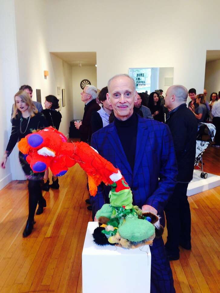 """John Waters, the filmmaker and curator of FraenkelLab's inaugural show """"Home Improvements"""" standing with an untitled work by artist collective Gelitin"""