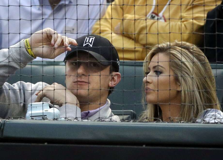 FILE  In this April 14, 2015, file photo, Cleveland Browns quarterback Johnny Manziel, left, sits with Colleen Crowley during a baseball game between the Los Angeles Angels and the Texas Rangers in Arlington, Texas. Dallas prosecutors say they will present the family violence case against troubled NFL quarterback Johnny Manziel to a grand jury this week. Manziel, a former Cleveland Browns quarterback and Heisman Trophy winner, is accused of hitting his ex-girlfriend Colleen Crowley during a night out in January.  (AP Photo/LM Otero, File) Photo: LM Otero, Associated Press