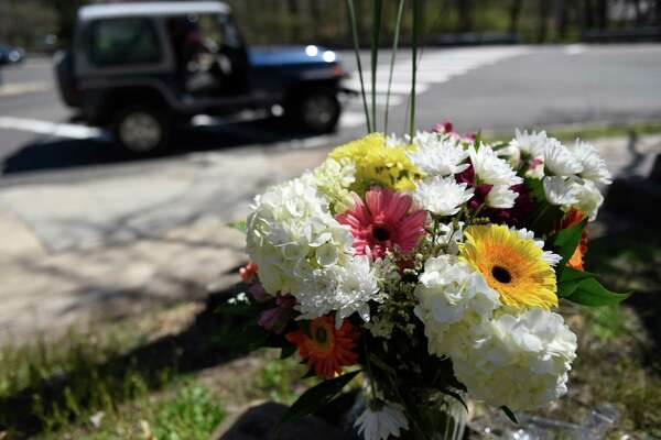 A bouquet of flowers in memory of hit and run victim Edward Setterberg, of Cos Cob, sits at the intersection of Hillside Road and East Putnam Avenue in Greenwich, Conn. Tuesday, April 19, 2016. Setterberg, 43, was struck by a vehicle around 11 p.m. Sunday at the intersection. Police announced that they had recovered the vehicle sought in connection with the fatality and tentatively identified the hit and run operator, but no charges have been filed yet.