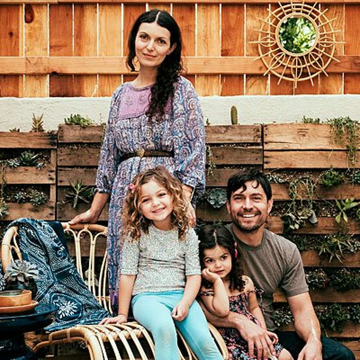"""Living wall Michelle and her husband, Tracy, wanted the yard to feel like an outdoor living room for them and Savannah (on the chair) and Saffron. A neighbor taught them how to make inexpensive living walls out of pallets. """"It's such a lovely addition to the garden,"""" Michelle says."""