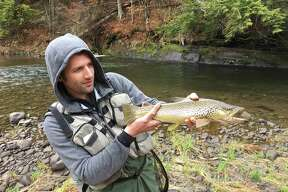 "Ken Wieczerza of Albany shows off a 20-inch brown trout he snared in the Catskills-area Williwemoc Creek over opening weekend of the season. The fish ""was worth the 4:30 a.m. drive from Albany and the morning rain,"" he said."