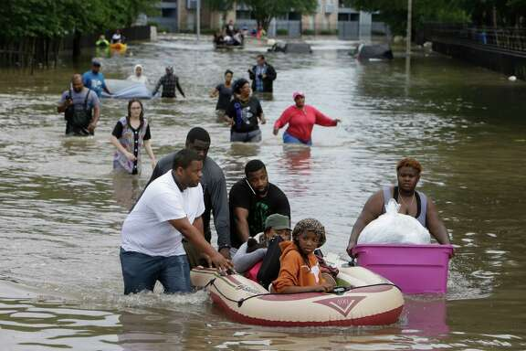 Residents of the Arbor Court Apartments help some of their neighbors to safety as they were forced to evacuate their flooded complex in the Greenspoint area on Monday. (Melissa Phillip/Houston Chronicle)
