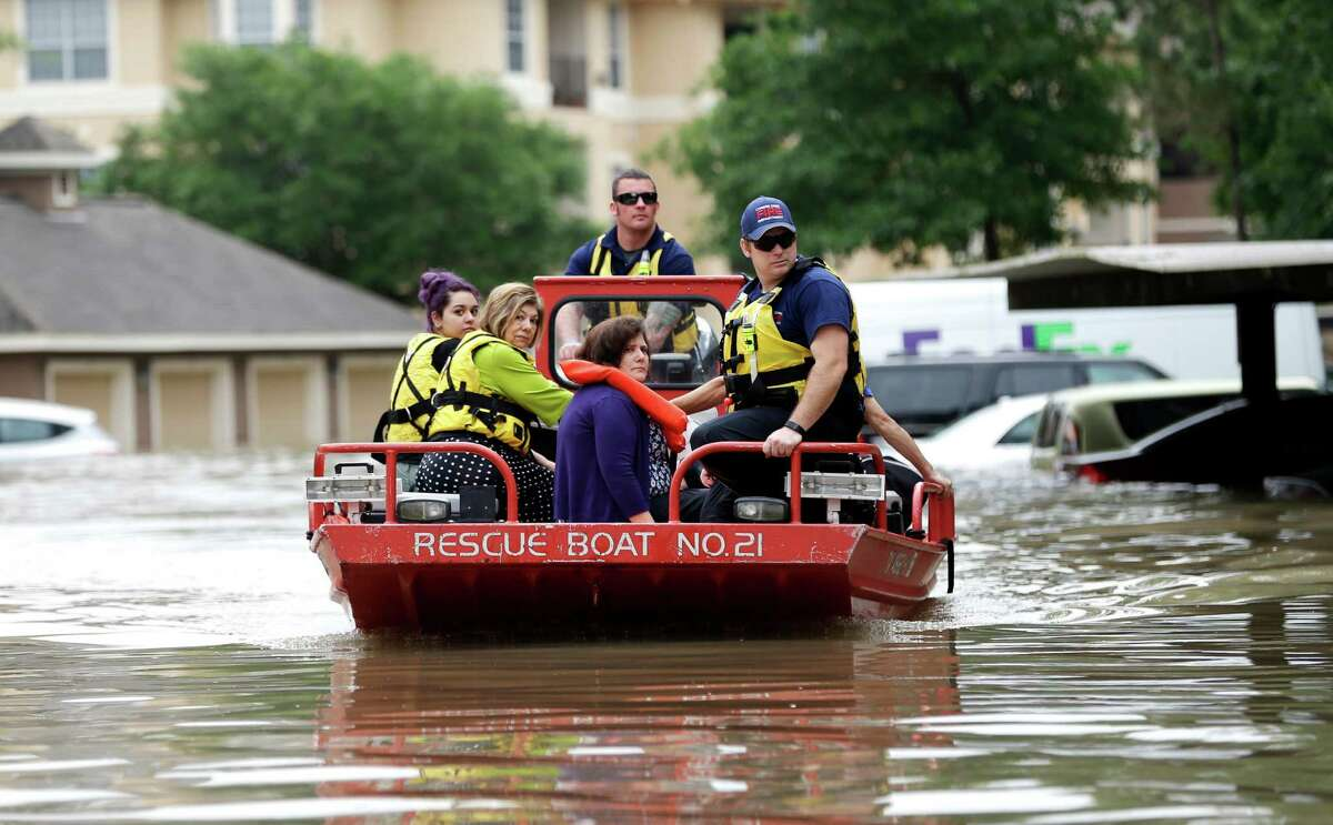 Residents are evacuated from their flooded apartment complex Tuesday, April 19, 2016, in Houston. Storms have dumped more than a foot of rain in the Houston area, flooding dozens of neighborhoods. (AP Photo/David J. Phillip) ORG XMIT: TXDP124