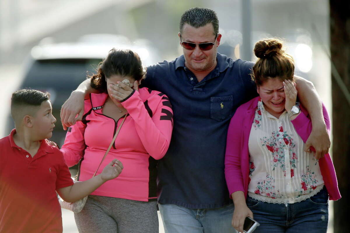 Linda Rodriguez, far right, along with other family members, react after seeing a white SUV, that is believed to belong to a 25-year-old family member, that was towed from the off ramp from the West Park Toll Way onto Post Oak Blvd. Tuesday, April 19, 2016, in Houston. The SUV was submerged in flood water caused by the recent storm. Tuesday, April 19, 2016, in Houston, Texas.
