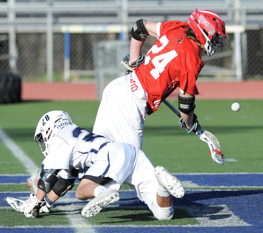 At right, Bailey Savio (#24) of Greenwich beats Benjamin Schwaeber (#28) of Staples on the face-off during the boys high school lacrosse match between Staples High School and Greenwich High School at Staples in Westport, Conn., Tuesday, April 19, 2016. Photo: Bob Luckey Jr. / Hearst Connecticut Media / Greenwich Time