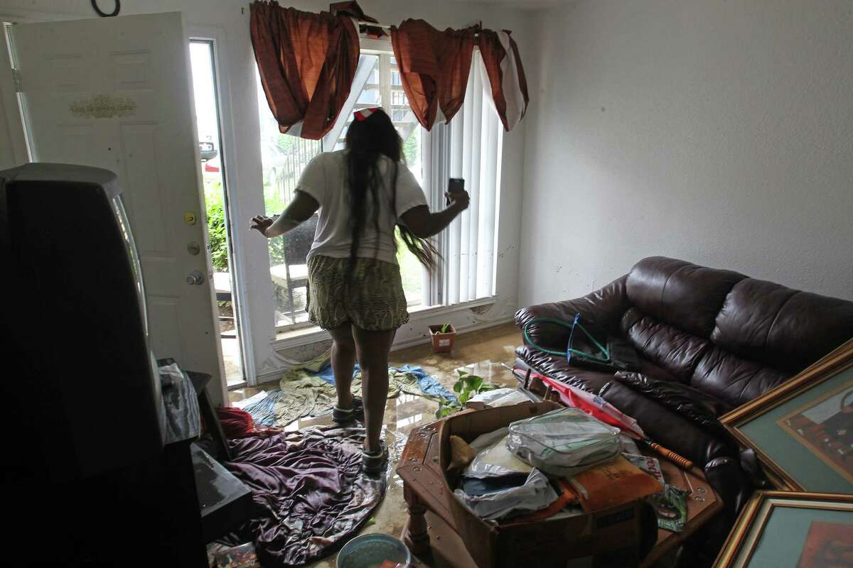 Chelsea Williams walks through the flooded living room of the Arbor Court apartment she shares with her mother, Janey.