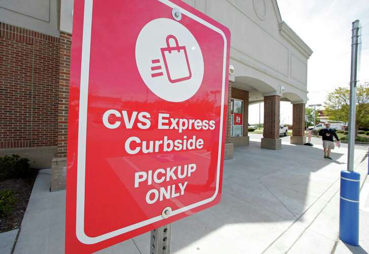 This April 15, 2016, photo shows a CVS Express parking sign at a CVS store in Harrisburg, N.C. Customers can shop via an app on their smartphone and will receive a text when their order is ready to be picked up. (AP Photo/Chuck Burton)