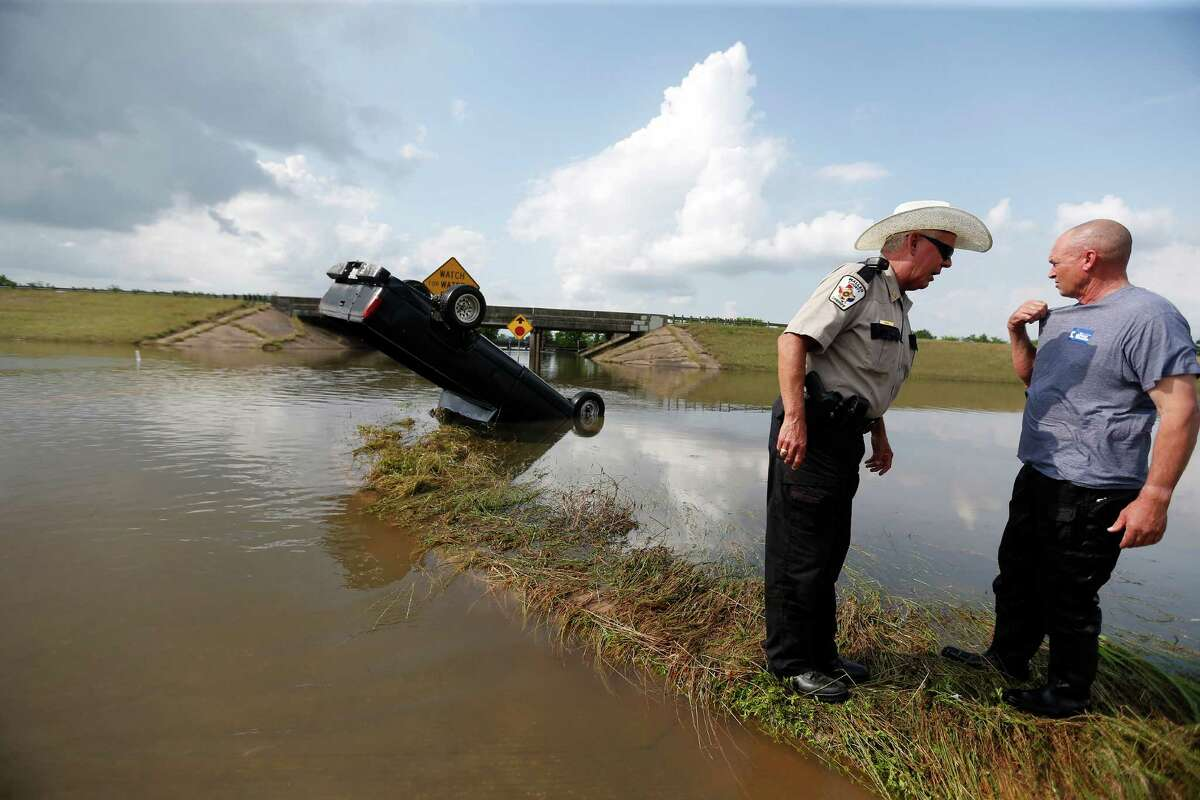 A truck sticks out of the floodwaters Tuesday at Interstate 10 in Brookshire after it was checked for possible victims. In just 12 hours, nearly 18 inches of rain walloped the area around the Waller County-Harris County line west of Houston.