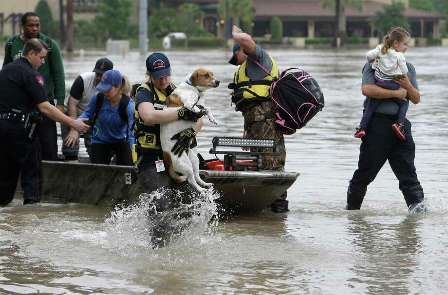 Emergency personnel help residents and their pets from a boat Tuesday after being evacuated from apartments on Cypresswood on the northwest side. Photo: Melissa Phillip, Staff / © 2016 Houston Chronicle
