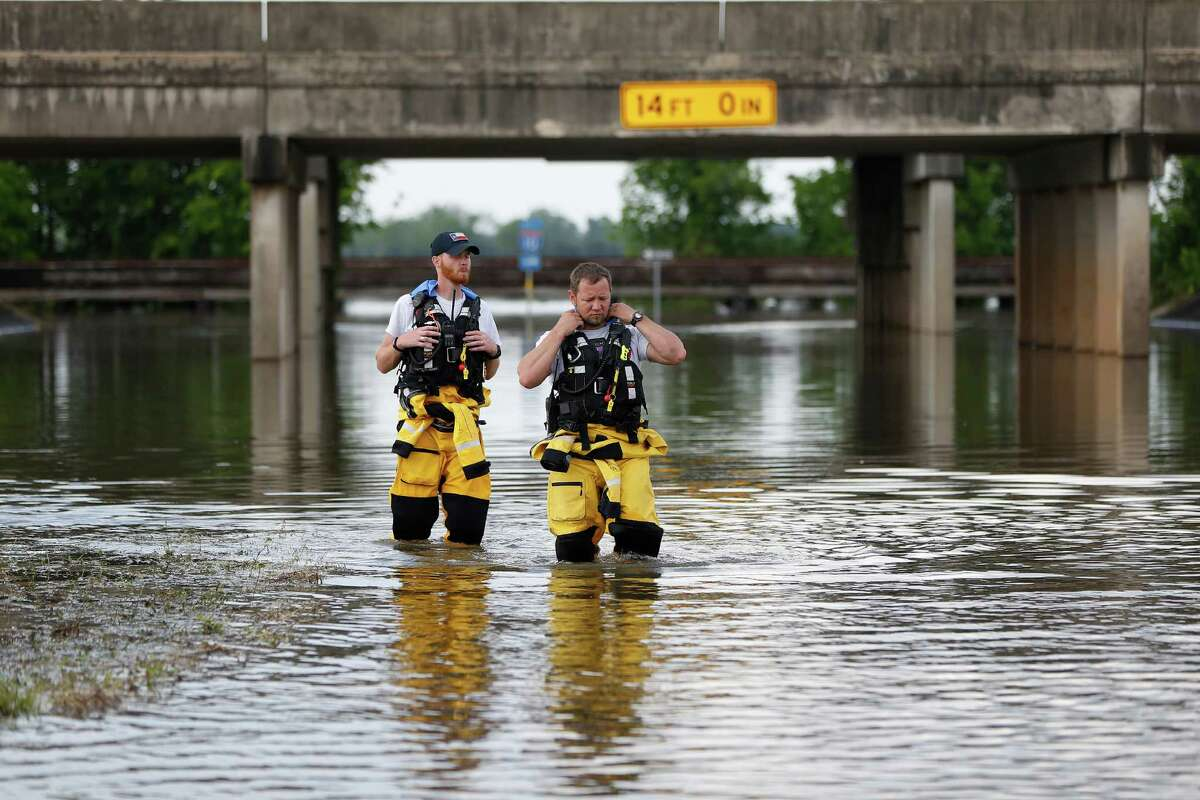 Texas Task Force 1,Taylor Leonard, left, and Gene Crow, right, walk through flood waters after on a frontage road of I-10, as they checked the contents of a truck that was submerged in the floods as they worked with the Texas Army National Guard and members of the Waller County County Judge and County Commissioners offices to assess damage in the area, Tuesday, April 19, 2016, in Brookshire.