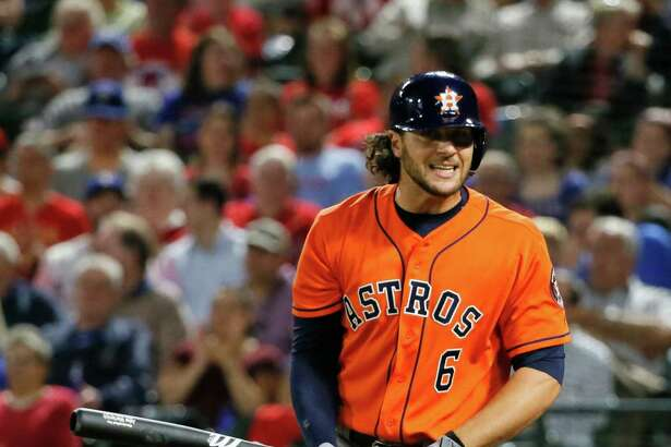 Astros outfielder Jake Marisnick spins away from the plate after striking out against the Rangers' Derek Holland in the fourth inning Tuesday night.