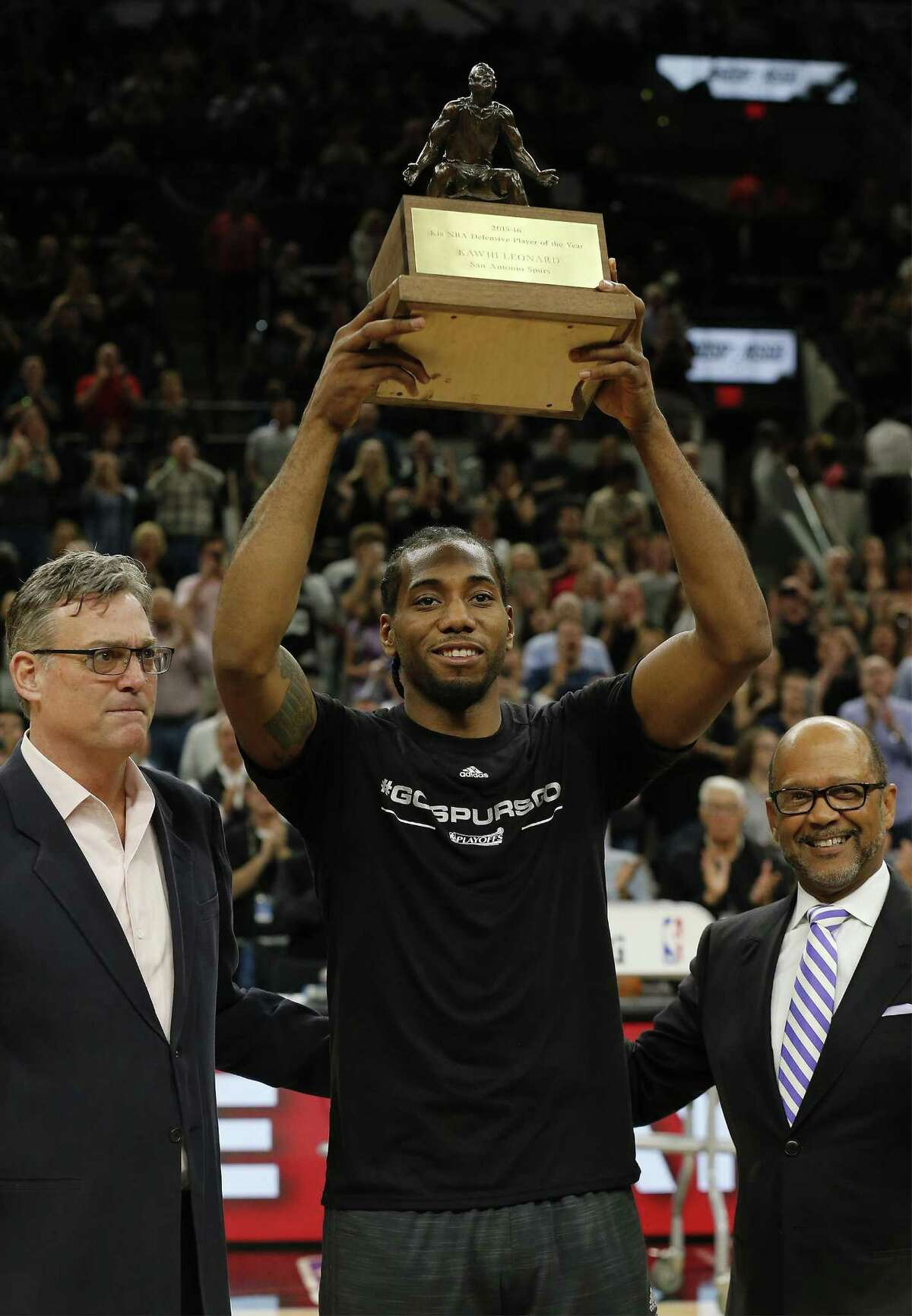 Spurs' Kawhi Leonard (center) holds up the NBA Defensive Player of the Year trophy alongside Spurs general manager R.C. Buford (left) before the start of Game 2 of a first-round playoff series against the Memphis Grizzlies at the AT&T Center on April 19, 2016.