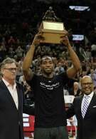 Spurs' Kawhi Leonard (center) holds up the NBA Defensive Player of the Year trophy alongside Spurs heneral manager R.C. Buford (left) before the start of Game 2 against the Memphis Grizzlies at the AT&T Center in the first round of Western Conference playoffs on April 19, 2016.