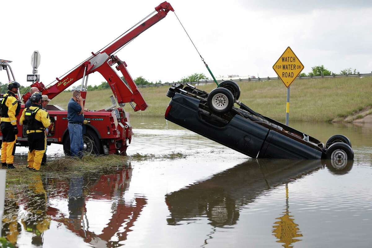 A truck sticks out of the floodwater at I-10 in Brookshire, after it was pulled up by a tow truck and members of the Texas Task Force 1, checked for possible victims, Tuesday, April 19, 2016, in Brookshire.