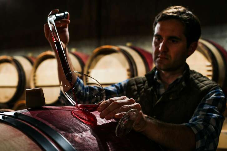 Winemaker Cory Empting uses a thief to take a sample of wine directly from the barrel, at Harlan Estate, a winery in Napa, California, on Tuesday, April 19, 2016.