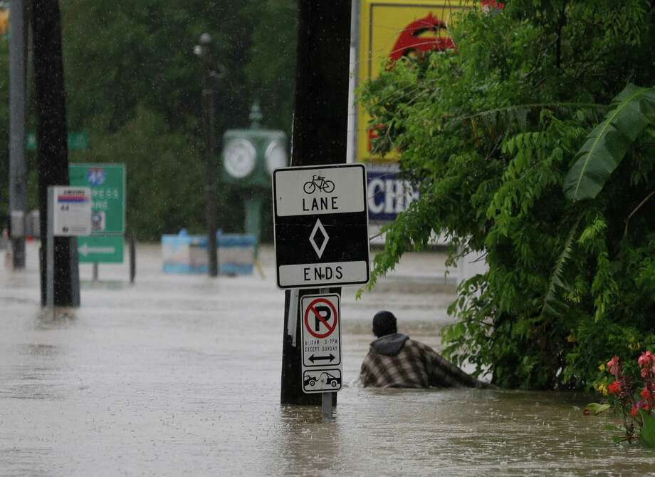 A man holds onto a fence as he wades through chest deep water along a flooded street Monday in Houston. Photo: Pat Sullivan /Associated Press / Copyright 2016 The Associated Press. All rights reserved. This material may not be published, broadcast, rewritten or redistribu