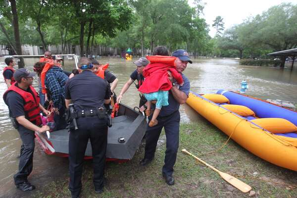 Spring Firefighter Kenneth Eisfeldt lifts 3-year-old Valerie Negrete to safety, Wednesday, April 20, 2016. The Negrete family had not been out of their home in One Westfield Lake Apartment since Sunday when flood waters began to swamp much of the Houston area. (Steve Gonzlaes / Houston Chronicle)