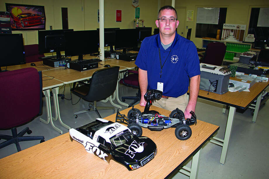 Matt Ruth, instructor of mechanical and architectural engineering and design at the Huron Area Technical Center, shows off the radio-controlled car that is entered in the mini portion of the Innovative Vehicle Design project sponsored by Square One Education Network.